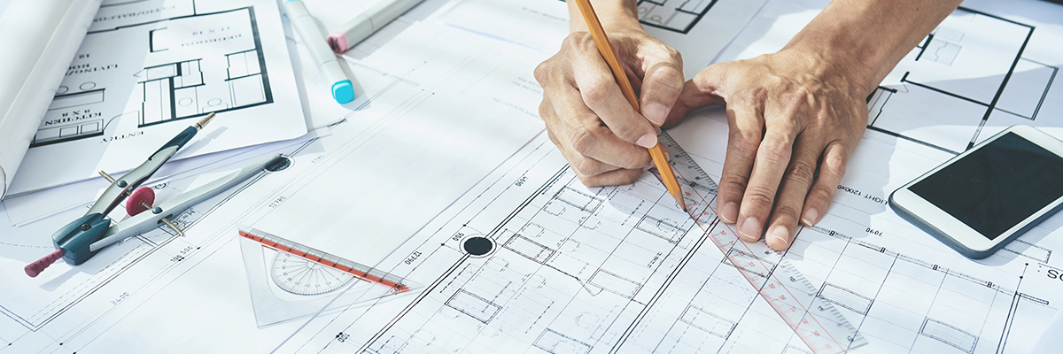 Close-up image of engineer drawing blueprint of building